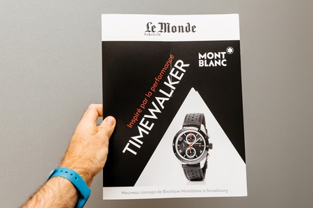 PARIS, FRANCE - NOV 19, 2017: Man holding against gray background a Le Monde newspaper supplement with advertising to Montblanc luxury watch and Timekeeper campaign Editorial