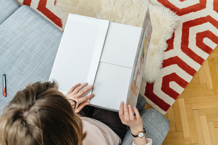 View from above of woman unboxing unpacking white cardboard box containing online shopping bought good