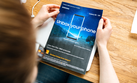 PARIS, FRANCE - APR 26, 2017: Woman reading Unbox Your Phone advertising campaign for Samsung Galaxy Smartphone S8 in French from Orange Telecom in magazine newspaper