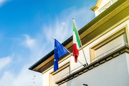 Italian and European union flags on the Embassy building on a sunny day in Strasbourg, France with sunlight flare
