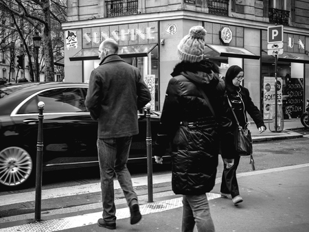 PARIS, FRANCE - JAN 30, 2018: French male and muslim female crossing street in front of Mercedes -Benz luxury limousine in Paris, on the Rue St Vincent de Paul - black and white