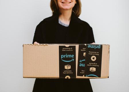 PARIS, FRANCE - FEB 16, 2018: Smiling elegant fashionista woman holding Amazon Prime cardboard parcel box against white background Editorial