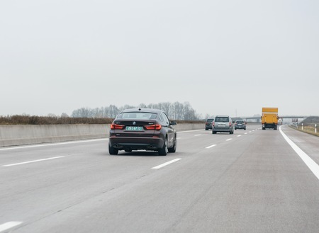 FRANKFURT, GERMANY - FEB 18, 2018: Driver POV personal perspective toward the driving BMW 535i GT luxury purple red car on the autobahn highway