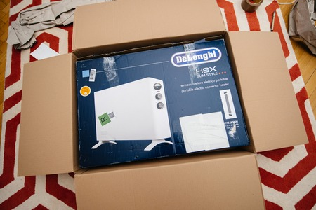 PARIS, FRANCE - FEB 7, 2018: Unboxing large cardboard box containing italian DeLonghi air convection heater bought from Amazon Warehouse Deals