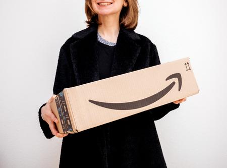 PARIS, FRANCE - FEB 16, 2018: Smiling elegant fashionista woman holding Amazon Prime cardboard parcel box against white background