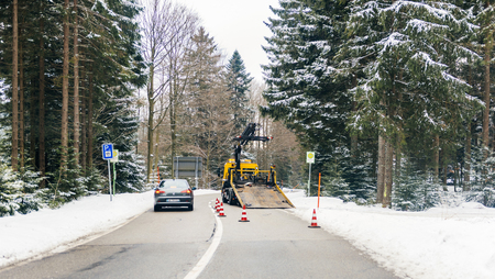 BADEN WURTTEMBERG, GERMANY - FEB 25, 2018: Driver point of view tow truck working security safety car from the ADAC car helping during accident in forest snowy road. ADAC is the abbreviation of Allgemeiner Deutscher Automobil-Club
