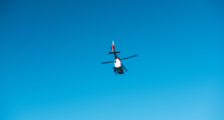 BADEN WURTTEMBERG, GERMANY - FEB 25, 2018: View from below of rescue helicopter DRF Luftrettung flying in clear blue sky transporting a victim to hospital