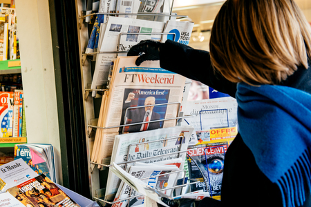 PARIS, FRANCE - JAN  21, 2017: Woman buying at media press kiosk the Financial Times Weekend edition featuring Donald Trump US President ant the America First slogan