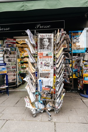 PARIS, FRANCE - MAR 15, 2018: Vertical photo International newspapes stack with portrait of Stephen Hawking the English theoretical physicist, cosmologist dead on 14 March 2018 on sale in Paris kisok