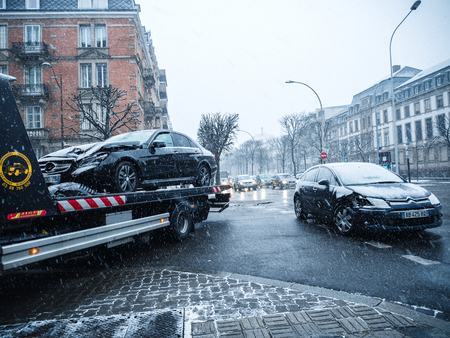 STRASBOURG, FRANCE - MAR 2, 2018: Car accident on French street between luxury limousine Mercedes-Benz and Citroen car on a snowy tempest cold day traffic jam tow truck