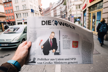 PARIS, FRANCE - MAR 19, 2017: Man reading buying German Die Welt newspaper at press kiosk featuring Russian presidential election from 2018 with the winner Vladimir Putin city background Standard-Bild - 98498027