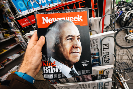 PARIS, FRANCE - MAR 19, 2017: Man reading buying Newsweek magazine featuring Benjamin Netanyahu aka Bibi Israeli politician serving as the 9th and current Prime Minister of Israel since 2009 Editorial
