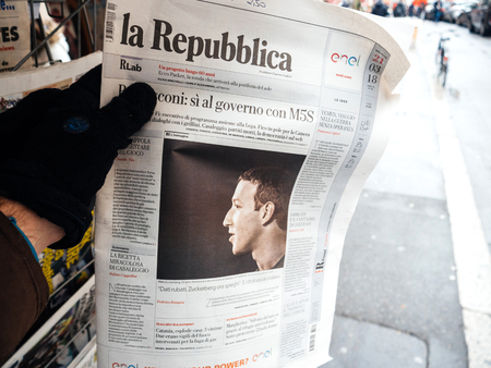 STRASBOURG, FRANCE  - MAR 22, 2018: Man reading buying Italian La Republica newspaper at press kiosk featuring Mark Zuckerberg, Facebook CEO - scandat data leaks from Cambridge Analytica Editorial