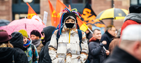 STRASBOURG, FRANCE  - MAR 22, 2018: Young boy with funny hat and mask at demonstration protest strike against Macron French government string of reforms - defocused crowd background