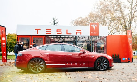 PARIS, FRANCE - NOV 29, 2014: New Tesla Model S showroom parked in front of the showroom with customers admiring the red electric luxury car Editorial
