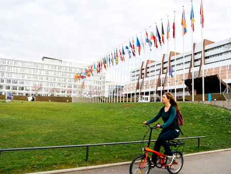 STRASBOURG, FRANCE - MAR 29, 2018: Woman on bike in front of Council of Europe with Flag of Russia flying half-mast as a tribute and mourning of victims of fire at Zimnyaya Vishnya Kemerovo