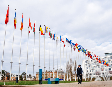 STRASBOURG, FRANCE - MAR 29, 2018: Worker under Flag of Russia flying half-mast at Council of Europe as a tribute and mourning victims of fire at Zimnyaya Vishnya shopping centre Kemerovo
