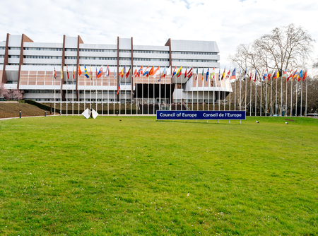STRASBOURG, FRANCE - MAR 29, 2018: Council of Europe sign, All Eu Flags and flag of Russia flying half-mast as a tribute and mourning of victims of fire at Zimnyaya Vishnya shopping centre Kemerovo