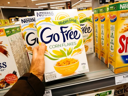 FRANKFURT, GERMANY - NOV 25, 2017: Male customer point of view buying Nestle Corn Flakes food in German supermarket Edeka - choosing the fresh healthy life food