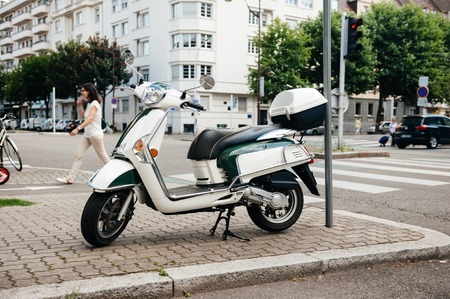 PARIS, FRANCE - JUN 27, 2015: Side view of modern Piaggio scooter parked on a French street Editorial