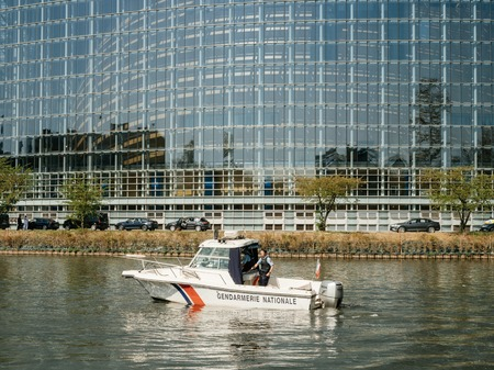STRASBOURG, FRANCE - APR 17, 2018: National Gendarmerie security boat near European Parliament facade during Emmanuel Macron visit in a bid to shore up support for his ambitious plans for post-Brexit reforms of EU Editorial