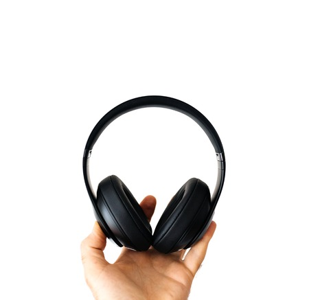 Man holding black headphones wireless headphones on white background Stock Photo