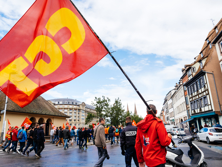 STRASBOURG, FRANCE - SEP 12, 2018: Man with CGT flag on street during a French Nationwide day of protest against labor reform proposed by Emmanuel Macron Government