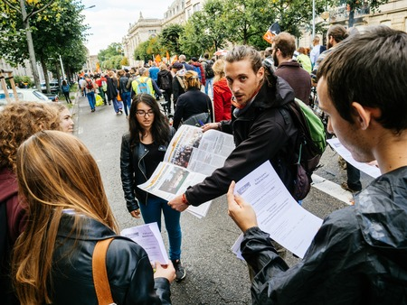 STRASBOURG, FRANCE - SEP 12, 2018: Man distributing manifests flyers newspapers during a French Nationwide day of protest against labor reform proposed by Emmanuel Macron Government