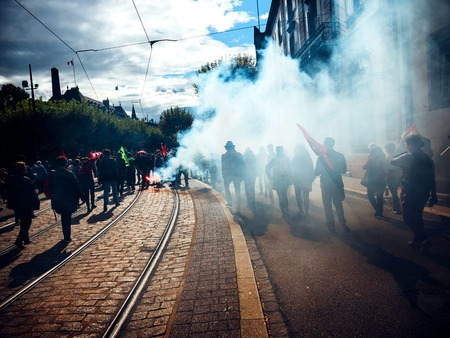 STRASBOURG, FRANCE - SEP 12, 2018: Smoke grenade thrown by people during French Nationwide day of protest against labor reform proposed by Emmanuel Macron Government