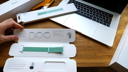 PARIS, FRANCE - APR 24, 2018: New Apple Watch Series 3 smartwatch change strap to the new 42mm Marine Green Sport Loop  - unboxing of strap and admiring the strap