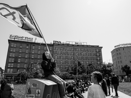 STRASBOURG, FRANCE - MAY 5, 2018: People making a party protest Fete a Macron in front of Gare de Strasbourg - young boy with anonymous mask waving communist flag