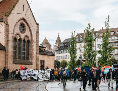 STRASBOURG, FRANCE - SEP 12, 2018: Closed street with crowd marching during a French Nationwide day of protest against labor reform proposed by Emmanuel Macron Government