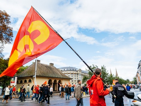 STRASBOURG, FRANCE - SEP 12, 2018: Central street with man waving CGT flag on street during a French Nationwide day of protest against labor reform proposed by Emmanuel Macron Government with police officer surveilling the protest Editorial