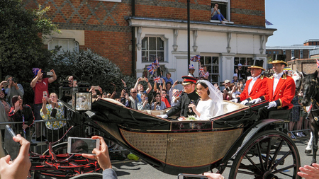 WINDSOR, ENGLAND - MAY 19 2018: Prince Harry, Duke of Sussex and Meghan, Duchess of Sussex leave Windsor Castle in Ascot Landau carriage during a procession after getting married at St Georges Chapel