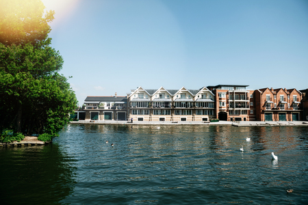 WINDSOR, BERKSHIRE, UNITED KINGDOM - MAY 19, 2018: Luxury houses on Tamisa river with swans and blue clear sky Editorial