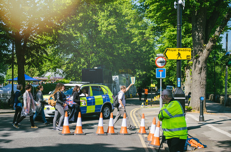 WINDSOR, UNITED KINGDOM - MAY 19, 2018: Tours group and Royal Wedding yellow street sign arrow during marriage of Prince Harry, Duke of Sussex and the Duchess of Sussex Meghan Markle
