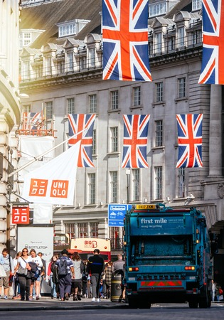 LONDON, UNITED KINGDOM - MAY 18, 2018: Garbage truck dustcart under Union Jack Flags on Regent Street a day before Royal Wedding between Prince Harry and Meghan Markle - unniqlo store