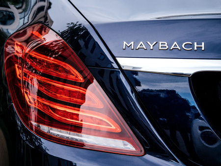 PARIS, FRANCE - MAY 21, 2018: Rear view of Maybach Mercedes logotype and red led stop light on new luxury blue Mercedes-Maybach s600 4matic awd limousine parked on street