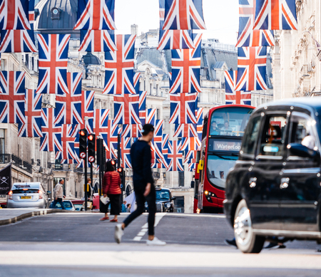 LONDON, UNITED KINGDOM - MAY 18, 2018: Defocused pedestrian silhouette under Union Jack Flags on Regent Street a day before Royal Wedding. The Royal Wedding between Prince Harry and Meghan Markle