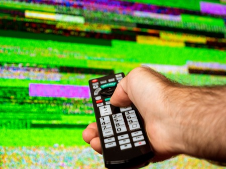 Man with large tv remote trying to fix the digital television noise on a large plasma OLED 4K Ultra HD High Dynamic Range HDR Smart TV .