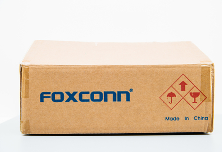 LONDON, UNITED KINGDOM - AUG 23, 2018: Unboxing Front view of Foxconn cardboard delivery box with logotype on against white background containing spare parts for computers laptop and technology part -