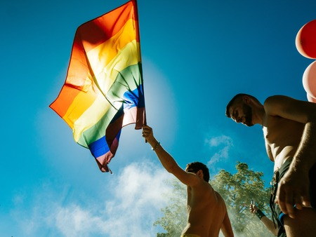 STRASBOURG, FRANCE - JUN 10, 2017: excited gay men people waving rainbow flag at Lesbian Gay Bisexual Transgender LGBT visibility march pride Festigays