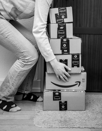 PARIS, FRANCE - JAN 13, 2018: Stack of Amazon Prime packages delivered to a home door woman trying to lift heavy boxes black and white Redactioneel