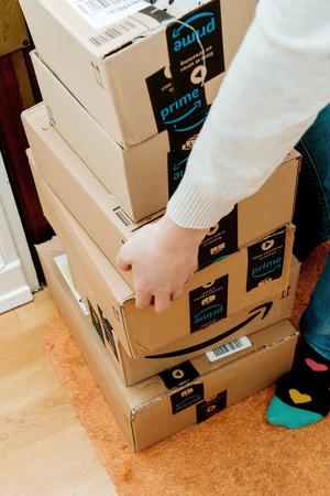 PARIS, FRANCE - JAN 13, 2018: Overhead shot of stack Amazon Prime packages delivered to a home door woman trying to lift heavy boxes