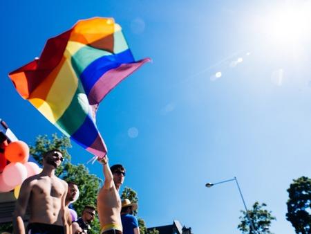 STRASBOURG, FRANCE - JUN 10, 2017: Defocused group of caucasian excited gay men waving rainbow flag against blue sky LGBT visibility march pride in Strasbourg