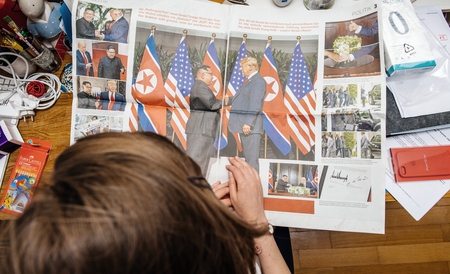 PARIS, FRANCE - JUNE 13, 2018: View from above of woman reading big article about U.S. President Donald Trump meeting North Korean leader Kim Jong-un in Singapore in German Die Welt