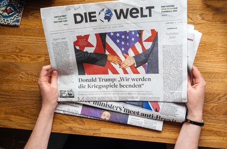 PARIS, FRANCE - JUNE 13, 2018: Woman reading German Die Welt newspaper in the office showing on cover  U.S. President Donald Trump meeting North Korean leader Kim Jong-un in Singapore Standard-Bild - 104474095