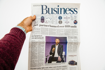 PARIS, FRANCE - JUN 13, 2018: Man holding The Daily Telegraph with portrait of Elon Musk CEO of tesla saying he is cutting 9 percent of jobs Editorial
