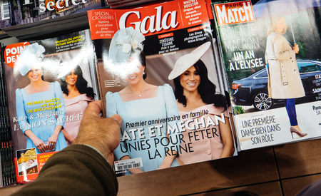 PARIS, FRANCE - CIRCA 2018 POV hand newspaper kiosk stand with Gala magazine showing Meghan Markle and Catherine Kate Middleton, Duchess of Cambridge