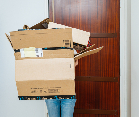 PARIS, FRANCE - JAN 13, 2018: Woman holding stack of Amazon Prime packages - hiding behind cardboard boxes Reklamní fotografie - 104474662